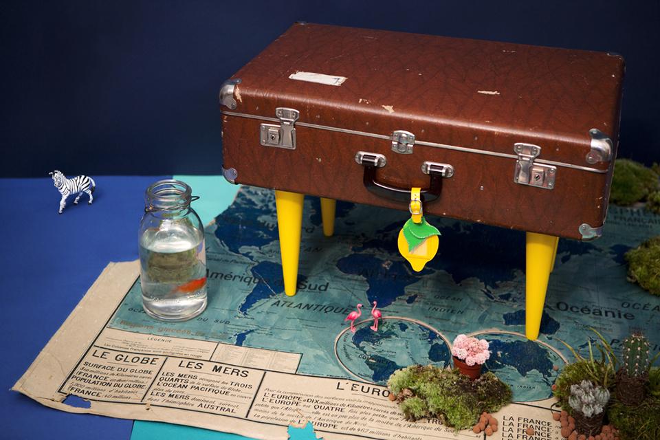 Scénographie plage valise table Tikilulu, une valise transformée en table et une carte du monde vintage